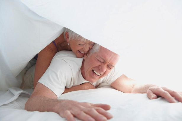 Elderly couple playing under sheet in bed